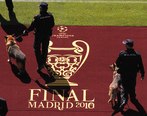 Police and their dogs walk past the logo for the Champions League final in Madrid on the eve of the soccer match