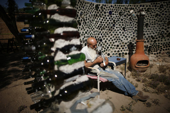 """Artist Roy Lohr sits in a """"spaceship"""" he built in his back yard from wine and beer bottles in Truth or Consequences, New Mexico"""