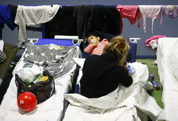 A migrant woman tends to a child at an improvised temporary shelter in a sports hall in Hanau