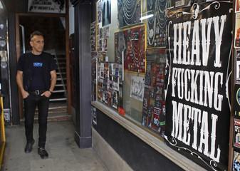 Pedro Paiva, 49, walks along the corridor of the building where he runs his shop in Lisbon