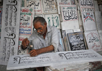 Abdul Razaq, 71, inscribes verses of the Koran on a gravestone at a shop in Lahore