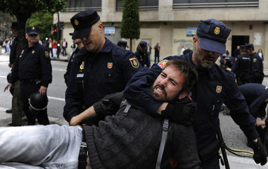 Spanish riot police remove activists of the group The Madrena during a rally in front of the occupied building in Oviedo