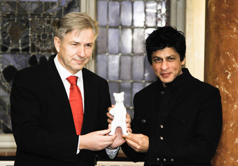 Indian actor Shah Rukh Khan holds a porcelain bear, the mascot of Berlin which he received from Mayor Klaus Wowereit after signing the city's guest book