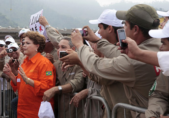 Employees of Brazilian oil giant Petrobras take pictures of Brazil's President Rousseff as she arrives for the opening ceremony of the P-56 oil rig at Angra dos Reis