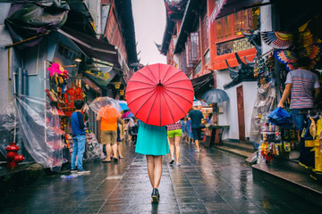 People woman walking in chinatown shopping street. Rainy day girl tourist under red oriental umbrella in narrow alleys on china travel in Shanghai.