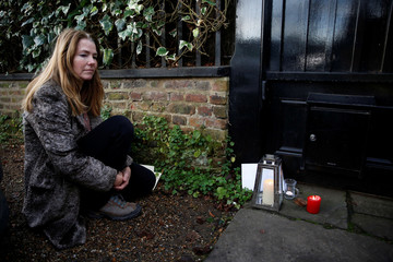 A woman leaves a tribute to singer George Michael outside of his home in north London