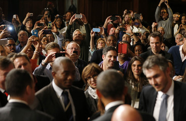 Members of the audience take pictures as U.S. President Barack Obama meets other members of the audience after delivering remarks at the University of Cape Town