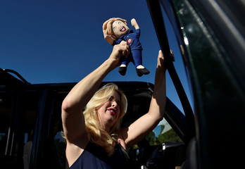 Mona Fishman of Las Vegas shakes a doll looking like Hillary Clinton before U.S. Republican presidential nominee Donald Trump speaks at a campaign rally in Henderson, Nevada