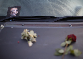 A photograph and rose lie on a car in tribute to singer George Michael outside of his home in north London