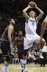 Dallas Mavericks' Nowitzki puts up a shot past Cleveland Cavaliers' Casspi during the first quarter of their NBA basketball game in Cleveland