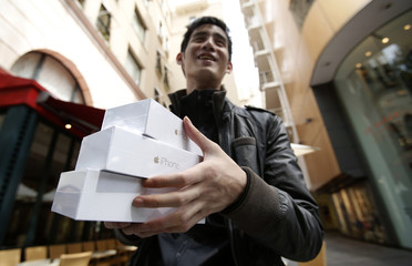 Canadian Jastin Leung holds some of his Apple iPhone 6 near the Apple Store at Tokyo's Omotesando shopping district