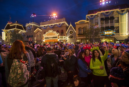 People wait for the park to open on Main Street at sunrise ahead of Disneyland's Diamond Celebration in Anaheim