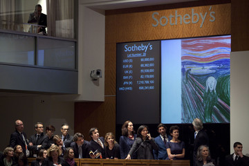 """Representatives speak to potential bidders on phones during an auction for Edvard Munch's painting entitled """"The Scream"""" at a Sotheby's auction in New York"""