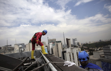Men dressed as comic book heroes Batman and Flash prepare to clean the glass facade of Hospital Infantil Sabara before meeting with patients of the children's hospital in Sao Paulo