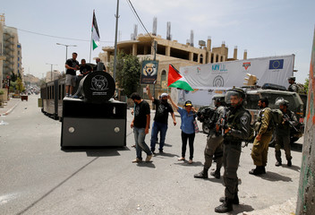 Israeli border policemen stand guard as Palestinians stand atop a mock train at a scene symbolising the return to homes that Palestinians lost during the 1948 war, in the West Bank town of Bethlehem
