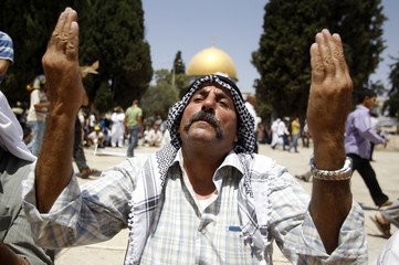 A Muslim man prays in front of the Dome of the Rock in Jerusalem's Old City