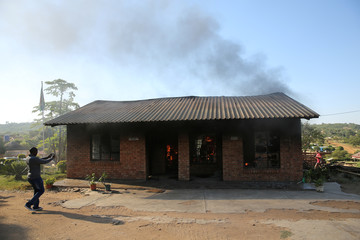 A man uses a cellphone to take pictures of a burning school office in Mashau Dolly village