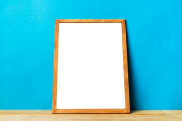 Blank wooden picture frame on wood table and blue wall, you can add text or picture in copy space for design,Template mockup background.
