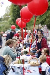 Neighbours sit at their tables during a street party to mark the Diamond Jubilee of Britain's Queen Elizabeth in Clapham, South London