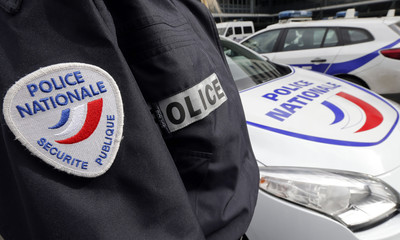 An illustration picture shows a French National Police insignia on the uniform of an officer who stands near parked cars outside the Police Headquarters in Bordeaux