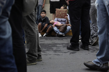 """A mother carries her daughter as she holds a poster, which reads, """"I want a country where they command the people, not the television,"""" as she takes part in a """"symbolic blockade"""" in front of broadcaster Televisa in Monterrey"""