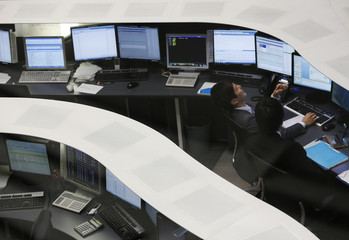 A Tokyo Stock Exchange employee laughs as he works at the bourse in Tokyo