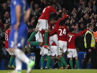 Swansea City's players celebrate after Graham scored against Chelsea during English League Cup semi-final soccer match in London