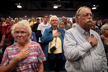 Audience members stand for the National Anthem before a campaign event with U.S Republican Vice Presidential candidate Mike Pence at the Des Moines Area Community College in Newton, Iowa