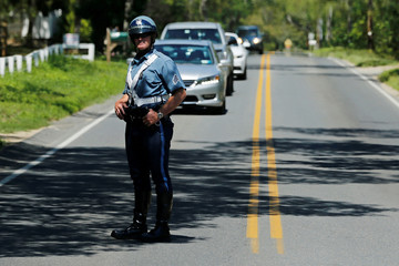 A police officer stops traffic as Obama travels in his motorcade to play golf at Farm Neck Golf Club during his annual summer vacation on Martha's Vineyard, Massachusetts, U.S.