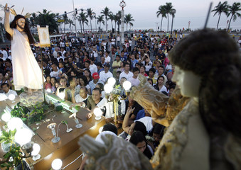 Catholic devotees attend procession of image of Risen Christ on Easter Sunday outside a church in Manila