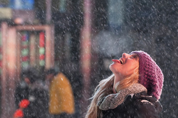 A tourist catches snowflakes on her tongue during snow fall in Times Square, Midtown, New York