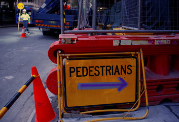 A sign indicates a route for pedestrians as a worker directs traffic at a construction site in central Sydney, Australia