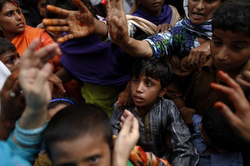 Flood victims try to grab aid distributed to their relief camp during Eid al-Fitr in Pakistan's Muzaffargarh district of Punjab province