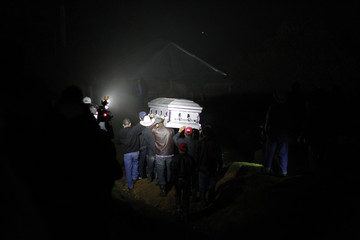 People carry the coffin of teenage migrant Ramos Juarez on a road leading to the village of San Jose Las Flores, Chiantla, in the Huehuetenango region