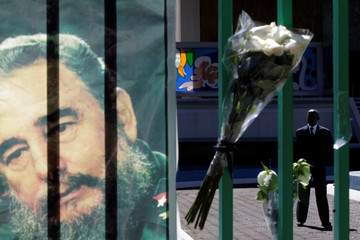 A security man stands behind a gate as flowers and a picture of the late Cuban revolutionary leader Fidel Castro are seen at the Cuba Embassy in Mexico City
