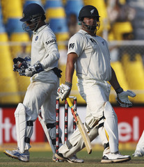 New Zealand's Ryder and India's captain and wicket keeper Dhoni are seen during the third day of their first test cricket match in Ahmedabad