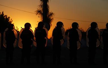 Anti-riot policemen stand guard outside a supermarket in San Fernando