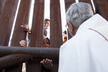 Tucson Diocese Bishop Kicanas offers Holy Communion through the border to the Mexico side of the fence, during a special mass at the United States and Mexico border near Nogales