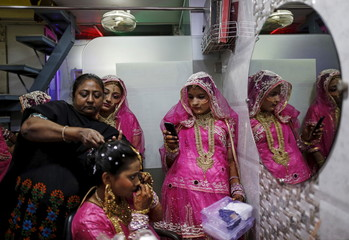 A Muslim bride gets her make-up done as another takes her picture at a beauty parlour before the start of a mass marriage ceremony in Mumbai