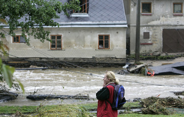 A woman reacts as she looks at flooded houses in the village of Hermanice