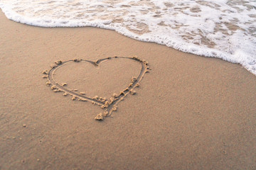 Heart shape hand writing on  sandy beach