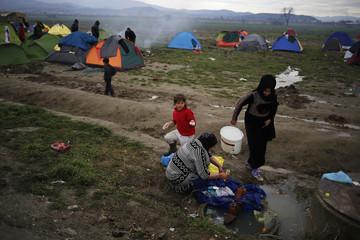 Migrants wash clothes at a makeshift camp on the Greek-Macedonian border, near the village of Idomeni