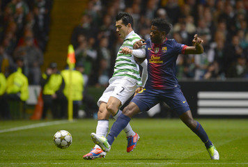 Barcelona's Alex Song is booked for his challenge on Celtic's Miku during their Champions League Group G soccer match at Celtic Park, Glasgow, Scotland