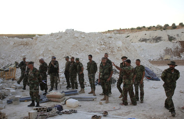 Forces loyal to Syria's President Bashar al-Assad inspect an underground base where caves were dug by rebel fighters in al-Hareeqa village, after the forces said they have regained control of the area in Hama countryside