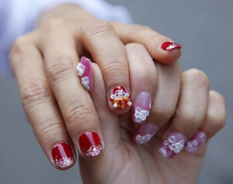 A woman gets a manicure with a mini figurine of the Chinese God of Wealth pasted on her nail before upcoming Chinese Lunar New Year celebrations in Taipei
