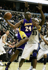 Bryant of the Los Angeles Lakers looks to pass the ball off as he drives around Haywood of the Washington Wizards during the second half of their NBA basketball game in Washington