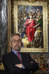 El Greco restorer Rafael Alonso stands underneath El Expolio painting in the sacristy of the Cathedral of Toledo