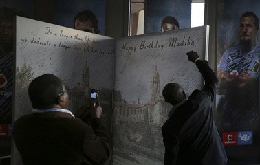 A well-wisher signs on a giant birthday card at the end of a soccer match between Manchester City and South Africa's Supersport United in support of the Nelson Mandela Football Invitational soccer in Pretoria