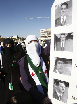 A Syrian woman living in Jordan holds a sign bearing pictures of Middle Eastern leaders during a demonstration in Amman