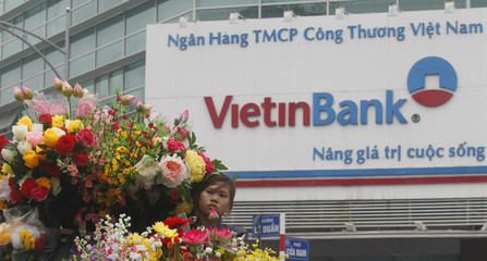 Woman transports artificial flowers for sale past a branch of Vietinbank in Hanoi